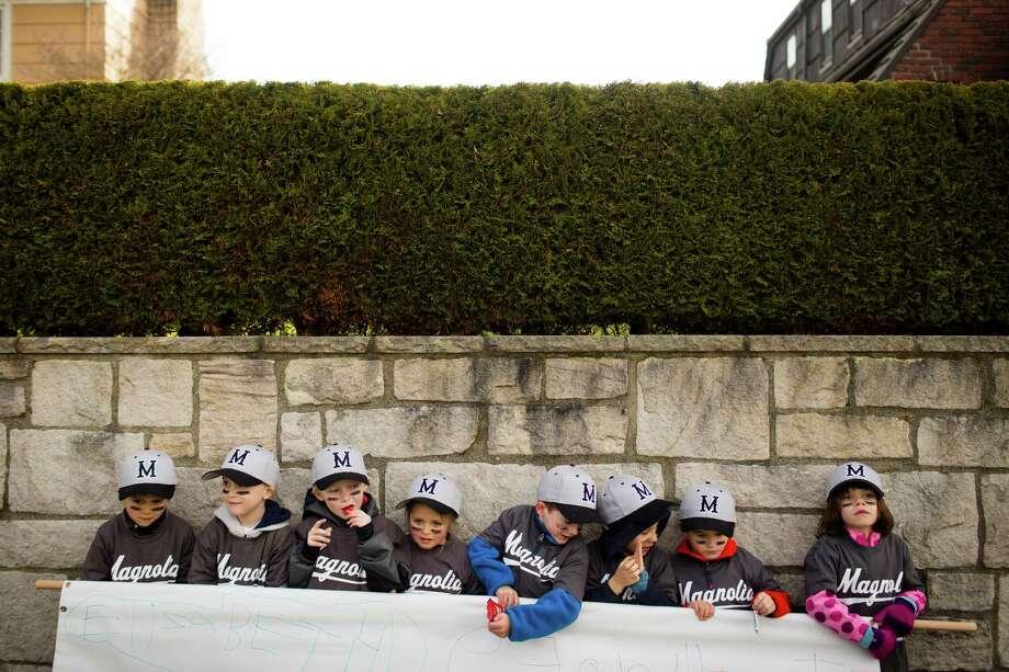 Kids struggle to hold up their team's sponsor sign for a parent photo op. Photo: JORDAN STEAD / SEATTLEPI.COM