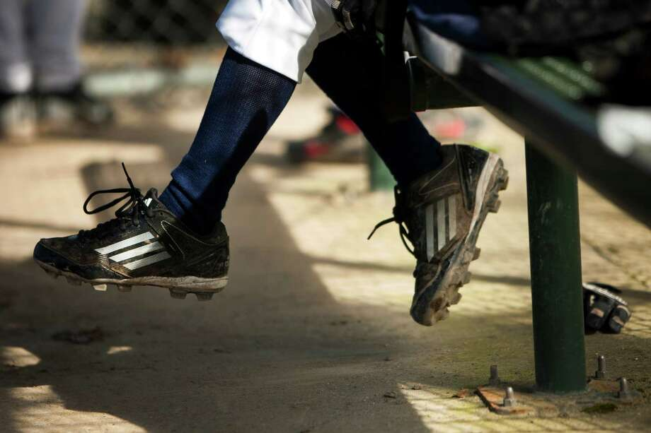 Little cleated feet fail to reach the dirt of the dugout at a scrimmage game following the parade. Photo: JORDAN STEAD / SEATTLEPI.COM