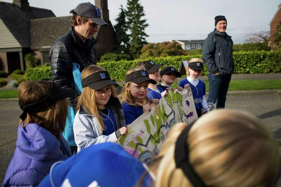 Girls prep their team sponsor's sign before the parade. Photo: JORDAN STEAD / SEATTLEPI.COM