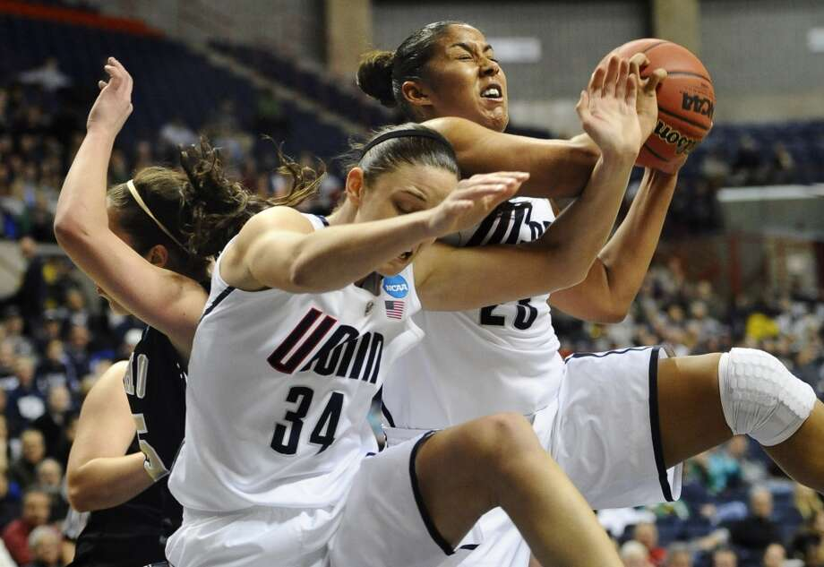 Connecticut's Kaleena Mosqueda-Lewis, right, pulls down a rebound against Idaho's Connie Ballestero, left, as Connecticut's Kelly Faris (34) defends in the second half of a first-round game in the women's NCAA college basketball tournament in Storrs, Conn., Saturday, March 23, 2013. Connecticut won 105-37. (AP Photo/Jessica Hill)