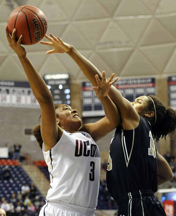 Connecticut's Morgan Tuck, left, goes up for a basket while guarded by Idaho's Ali Forde, right, during the first half of a first-round game in the women's NCAA college basketball tournament in Storrs, Conn., Saturday, March 23, 2013. Connecticut won 105-37. (AP Photo/Jessica Hill)