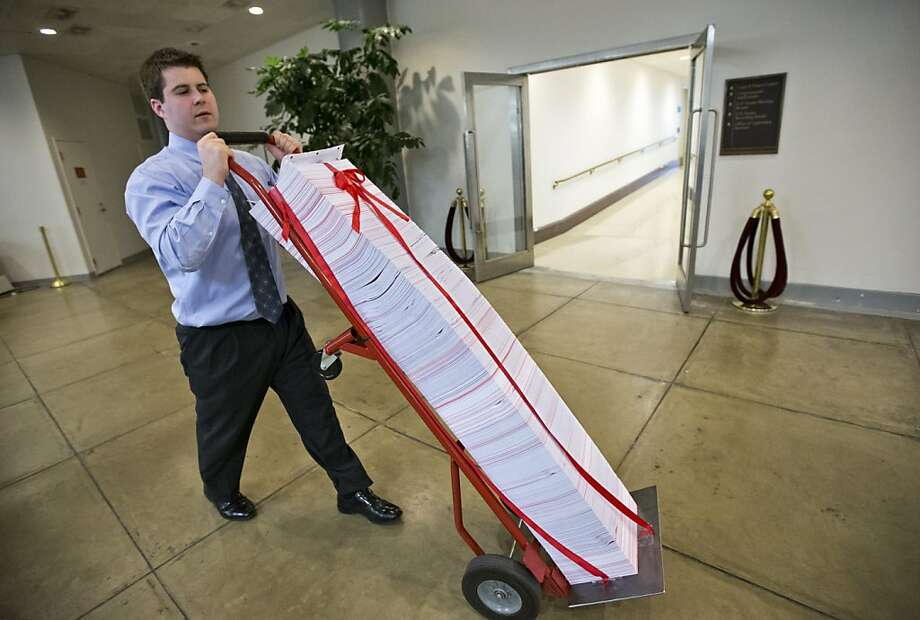 A Senate aide with a stack of documents  being used as a prop during debate on the Affordable Care Act. Photo: J. Scott Applewhite, Associated Press