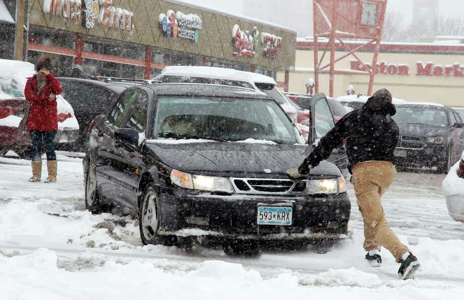 People work to free up a stuck car in a parking lot in central Denver as a spring storm packing high winds and heavy snow sweeps over Colorado's Front Range and on to the eastern plains on Saturday, March 23, 2013. Forecasters predict up to a foot of snow will fall in some locations in Colorado before the storm heads toward the nation's midsection. (AP Photo/David Zalubowski) Photo: David Zalubowski, Associated Press / AP