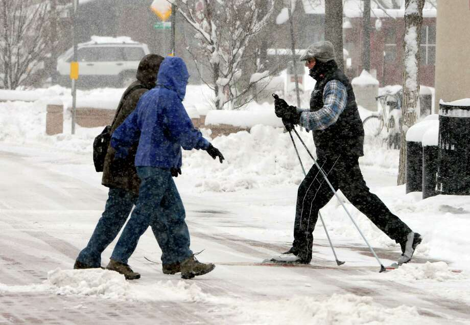 Joel Daly, right, uses his cross country skis to move in the snow near the Pearl Street Mall in Boulder, Colo. on Saturday, March 23, 2013. (AP Photo/The Daily Camera, Cliff Grassmick) NO SALES Photo: Cliff Grassmick, Associated Press / Daily Camera