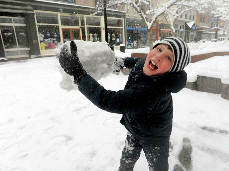 Jackson Bucklew, 7, visiting from Chicago, tosses a chunk of ice while playing in the snow near the Pearl Street Mall in Boulder, Colo. on Saturday, March 23, 2013. (AP Photo/The Daily Camera, Cliff Grassmick) NO SALES Photo: Cliff Grassmick, Associated Press / Daily Camera