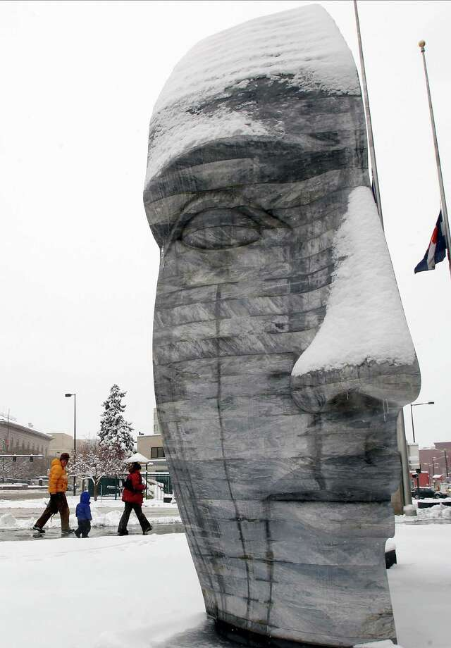 Pedestrians pass by the snow-covered sculpture of the double-headed Janus of Greek mythology by artist Larry Kirkland in Denver as a spring storm packing high winds and heavy snow sweeps over Colorado's Front Range and on to the eastern plains on Saturday, March 23, 2013. Forecasters predict up to a foot of snow will fall in some locations in Colorado before the storm heads toward the nation's midsection. (AP Photo/David Zalubowski) Photo: David Zalubowski, Associated Press / AP