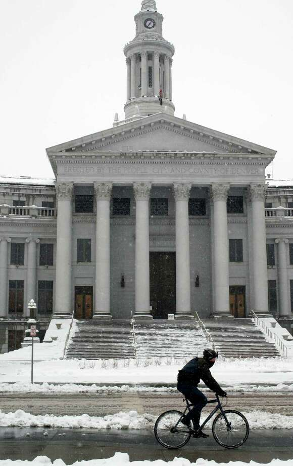A lone bicyclist rides past the Denver City/County Building in Denver as a spring storm packing high winds and heavy snow sweeps over Colorado's Front Range and on to the eastern plains on Saturday, March 23, 2013. Forecasters predict up to a foot of snow will fall in some locations in Colorado before the storm heads toward the nation's midsection. (AP Photo/David Zalubowski) Photo: David Zalubowski, Associated Press / AP