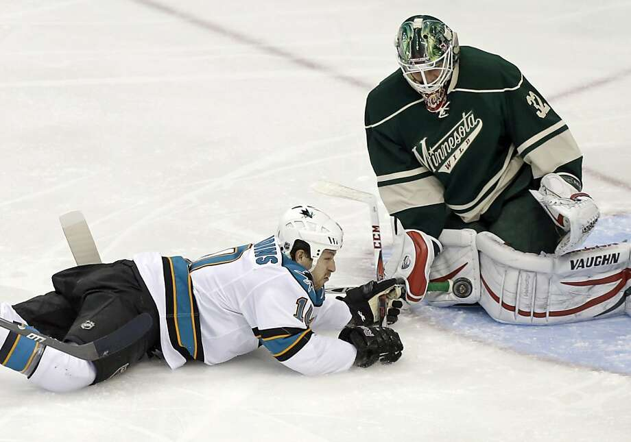 The Sharks' Andrew Desjardins slides into Wild goalie Niklas Backstrom after being tripped from behind. Desjardins was awarded a penalty shot, but Backstrom swatted it aside. Photo: Jim Mone, Associated Press