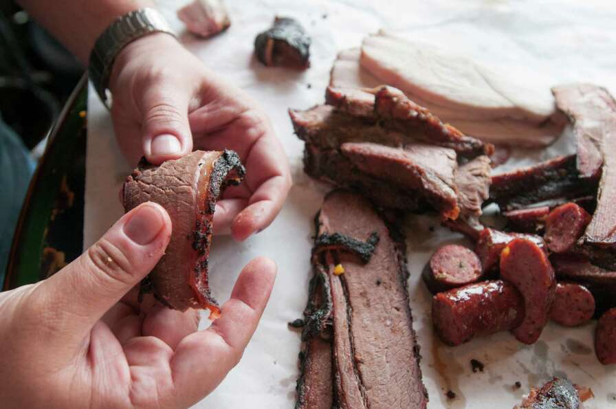 Daniel Vaughn, a barbecue aficionado and the Texas Monthly barbecue editor, handles a slice of barbe
