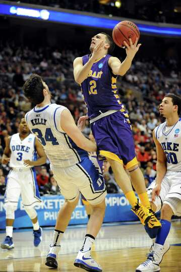 UAlbany's Peter Hooley, center, goes to the hoop and draws a foul from Duke's Ryan Kelly during thei