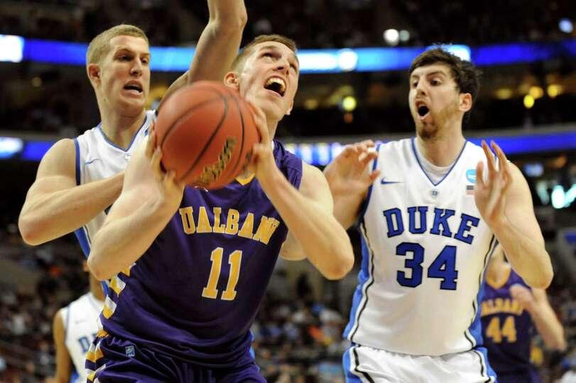 UAlbany's Luke Devlin, center, looks to shoot as Duke's Mason Plumlee, left, and Ryan Kelly defend d