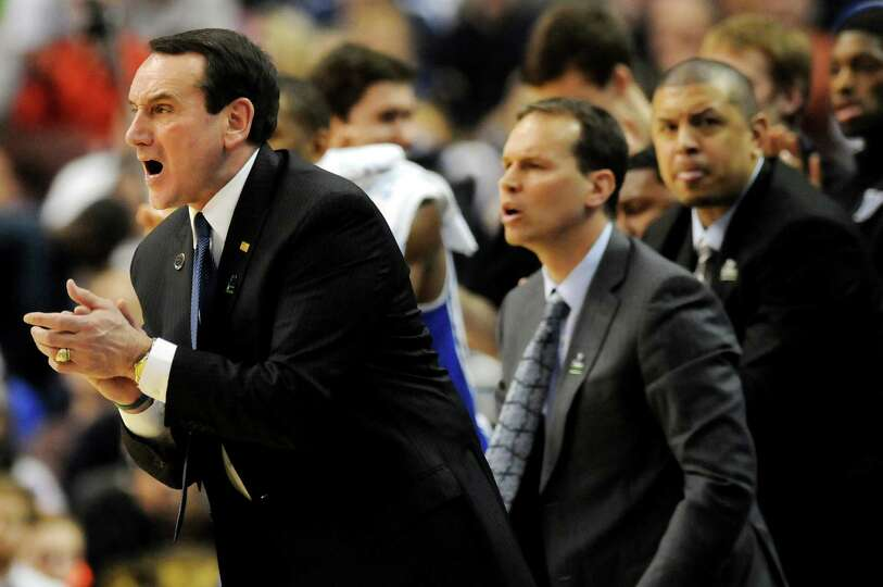 Duke's coach Mike Krzyzewski, left, instructs his team during their second round NCAA Tournament aga