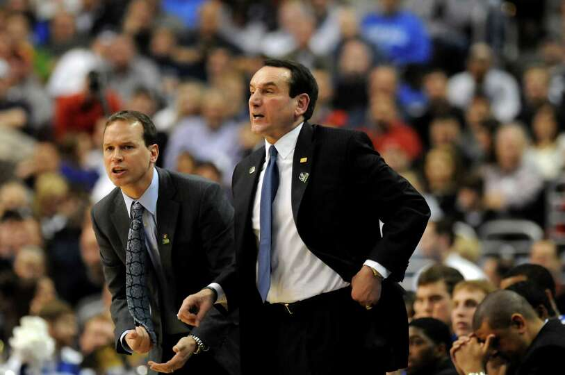 Duke's coach Mike Krzyzewski, right, instructs his team during their second round NCAA Tournament ag