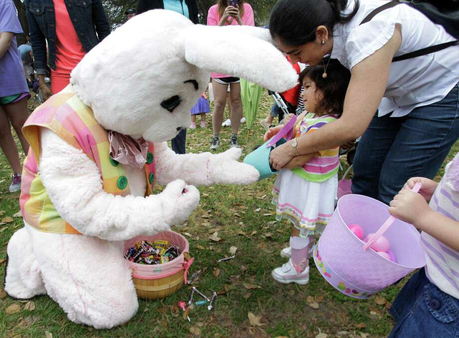 Claudia Soto helps her daughter, Isabel Barreda, 2, exchange beeping eggs for candy with the Easter bunny during the Beeping Easter Egg Hunt at The Lighthouse of Houston Community Services Center in Houston.  Blind and visually impaired children took part in the annual Beeping Easter Egg Hunt that also included a hay ride by the Houston Farm and Ranch Club, games, face painting, and music. Photo: Melissa Phillip, Houston Chronicle / © 2013  Houston Chronicle