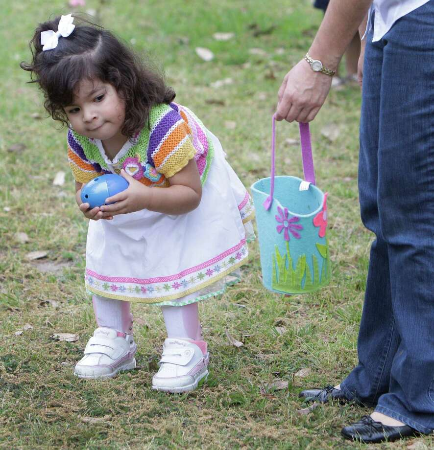 Isabel Barreda, 2,  picks up a beeping egg as her mom, Claudia Soto holds the basket, during activities at the Beeping Easter Egg Hunt. Photo: Melissa Phillip, Houston Chronicle / © 2013  Houston Chronicle