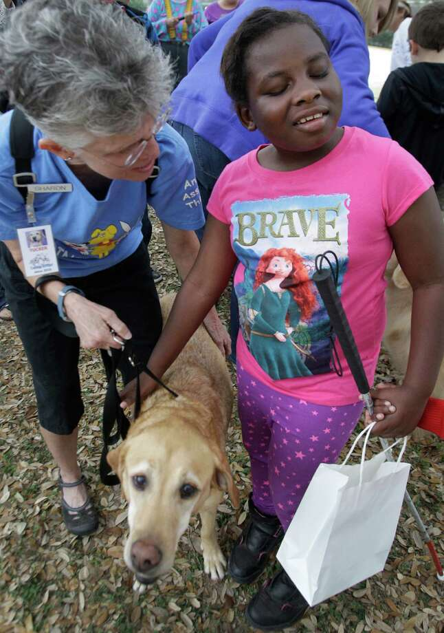Caring Critters member Sharon Schrinner, left, helps Ariyah Malone, 9, to pet her dog, Tucker, during activities at the Beeping Easter Egg Hunt. Photo: Melissa Phillip, Houston Chronicle / © 2013  Houston Chronicle