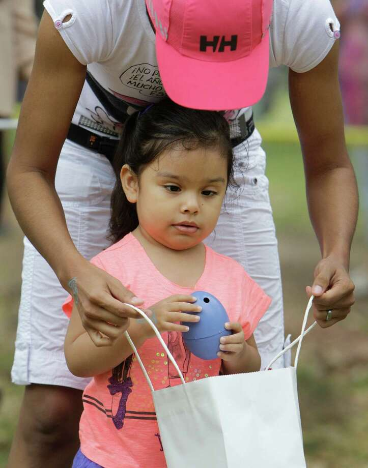 Genesis Hernandez helps her niece Daria Galindo, 4, during the Beeping Easter Egg Hunt. Photo: Melissa Phillip, Houston Chronicle / © 2013  Houston Chronicle