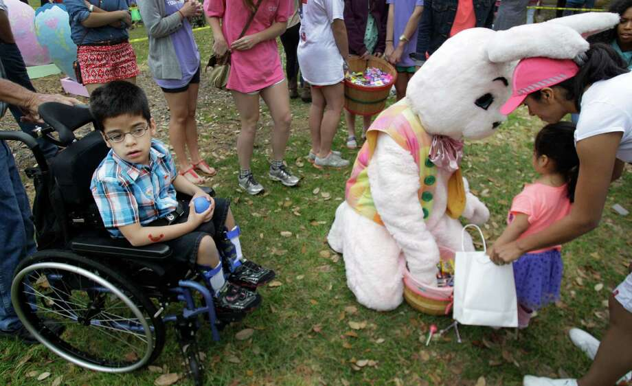 Christopher Jurek, 6, left, waits his turn in line as Genesis Hernandez, right,  helps her niece Daria Galindo, 4, exchange beeping eggs for candy with the Easter bunny during the Beeping Easter Egg Hunt at The Lighthouse of Houston Community Services Center. Photo: Melissa Phillip, Houston Chronicle / © 2013  Houston Chronicle