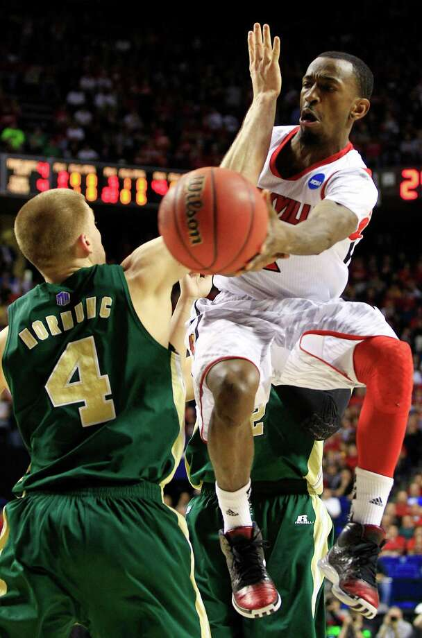 Louisville guard Russ Smith, right, passes the ball as Colorado State forward Pierce Hornung (4) defends during the first half of a third-round NCAA college basketball tournament game on Saturday, March 23, 2013, in Lexington, Ky. (AP Photo/James Crisp) Photo: James Crisp, Associated Press / FRE6426 AP