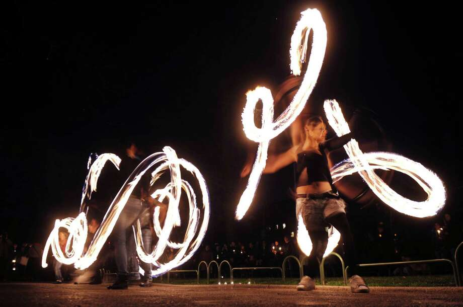 Fire acrobats perform in front of the Bulgarian National Theatre, with lights turned off, as part of the Earth Hour in Sofia on March 23, 2013. Millions of people were expected to switch off their lights for Earth Hour on March 23 in a global effort to raise awareness about climate change that was even to be monitored from space. Photo: NIKOLAY DOYCHINOV, AFP/Getty Images / AFP