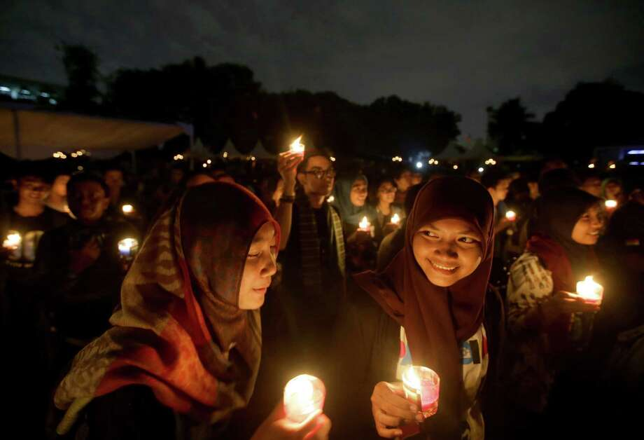 "Muslim women light candles during the ""EarthHour"" in Jakarta, Indonesia, Saturday, March 23, 2013. Hundreds of people gathered in Jakarta Friday to observe the global event that encourages people to turn off their lights for 60 minutes. Photo: Dita Alangkara, Associated Press / AP"
