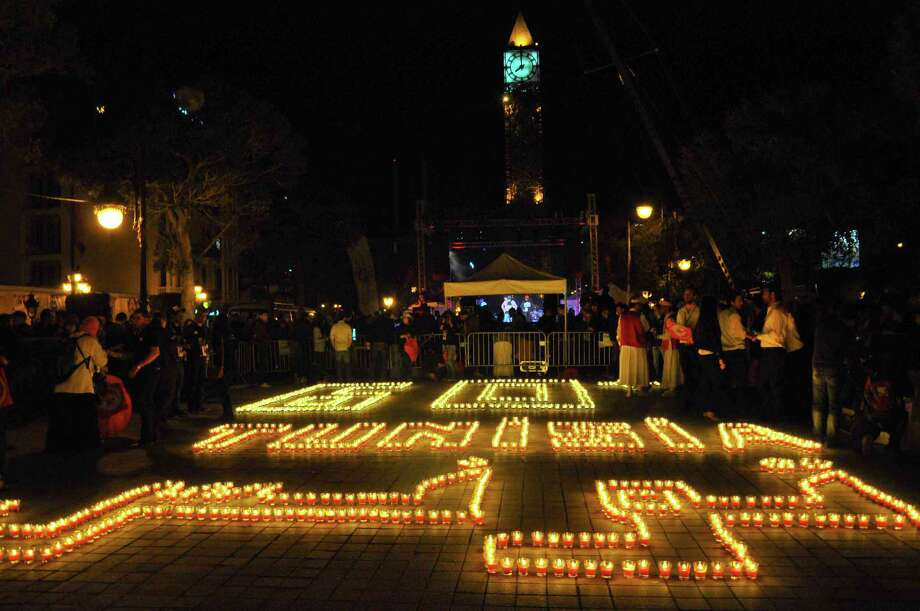 "This picture shows people standing next to candles arranged to read ""Tunisia"" in the Habib Bourguiba avenue after submerging into darkness as part of the Earth Hour switch-off in Tunis on March 23, 2013. Organisers expect hundreds of millions of people across more than 150 countries to turn off their lights for 60 minutes on Saturday night -- at 8:30 pm local time -- in a symbolic show of support for the planet. While more than 150 countries joined in last year's event, the movement has spread even further afield this year, with Palestine, Tunisia, Suriname and Rwanda among a host of newcomers pledging to take part. Photo: SAFA LAAMIRI, AFP/Getty Images / AFP"