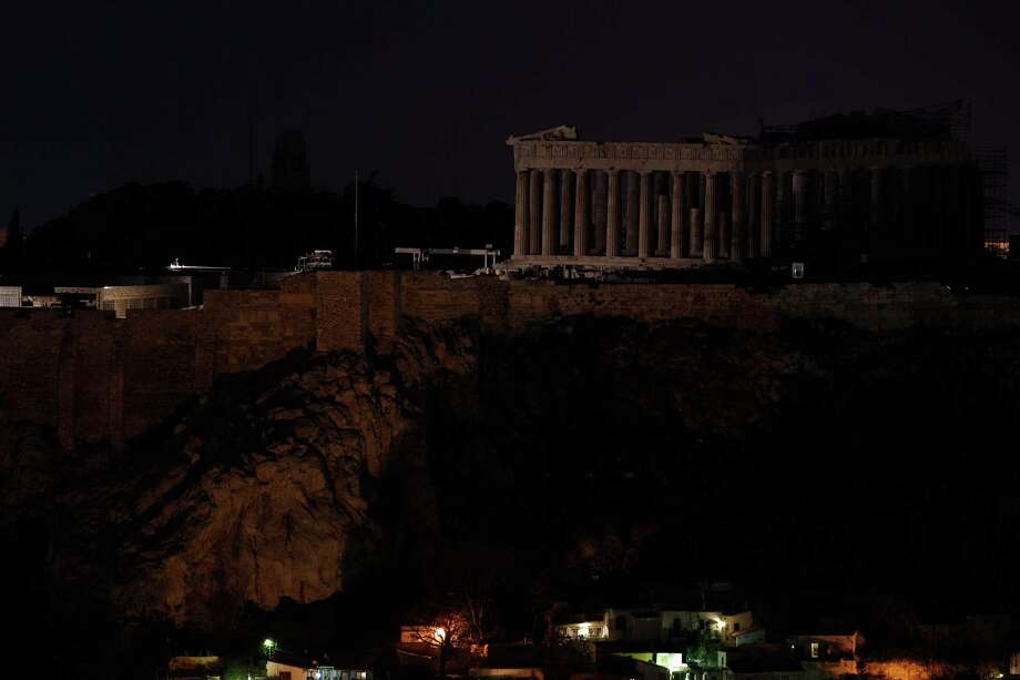 The Parthenon temple stands atop the Acropolis hill after turning off lights, to mark the annual Earth Hour in Athens, Saturday March 23, 2013. In Greece, floodlights in several monuments and public buildings were switched off for one hour at 8:30 p.m. local time. Thousands of businesses and municipalities also dimmed their lights. Photo: Kostas Tsironis, Associated Press / AP