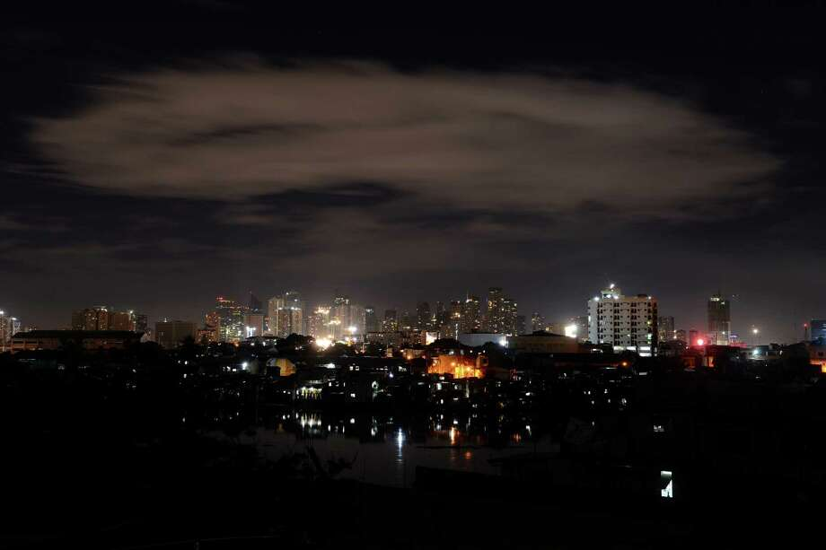 This general shot shows buildings from Manila's financial district after the lights were turned off to mark Earth Hour in Manila on March 23, 2013. Millions of people were expected to switch off their lights for Earth Hour on March 23, in a global effort to raise awareness about climate change. Since it began in Sydney in 2007, Earth Hour has grown to become what environmental group WWF says is the world's largest demonstration of support for action on carbon pollution. Photo: NOEL CELIS, AFP/Getty Images / AFP