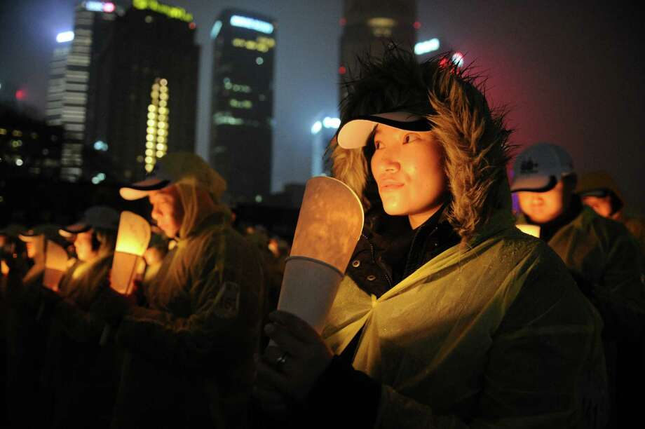 "People light candles as they take part in an event to promote ""Earth Hour"" in the financial district of Shanghai on March 23, 2013. Iconic landmarks and skylines were plunged into darkness as the ""Earth Hour"" switch-off of lights around the world got under way including China's commercial hub of Shanghai to raise awareness of climate change. Photo: PETER PARKS, AFP/Getty Images / AFP"