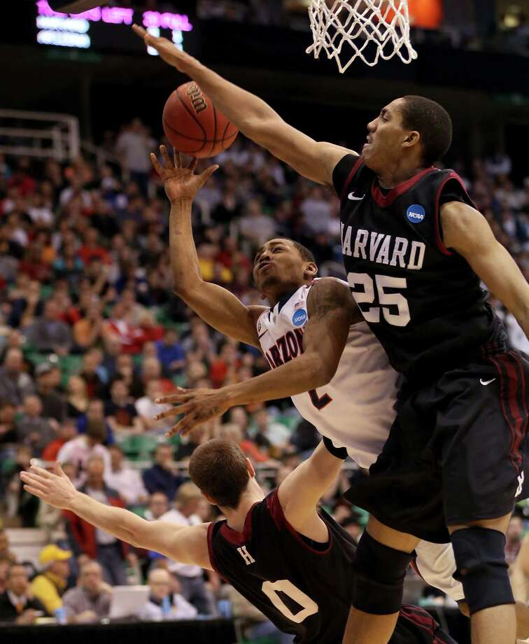 SALT LAKE CITY, UT - MARCH 23:  Mark Lyons #2 of the Arizona Wildcats goes up for a shot between Kenyatta Smith #25 and Laurent Rivard #0 of the Harvard Crimson in the second half during the third round of the 2013 NCAA Men's Basketball Tournament at EnergySolutions Arena on March 23, 2013 in Salt Lake City, Utah. Photo: Streeter Lecka, Getty Images / 2013 Getty Images