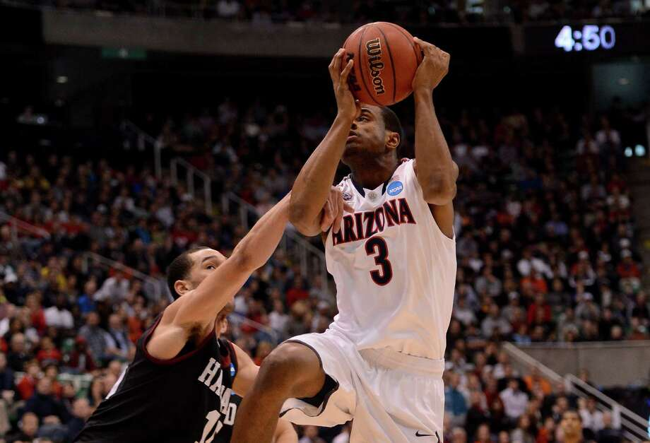 SALT LAKE CITY, UT - MARCH 23:  Kevin Parrom #3 of the Arizona Wildcats is fouled by Christian Webster #15 of the Harvard Crimson as he goes up for a shot in the first half during the third round of the 2013 NCAA Men's Basketball Tournament at EnergySolutions Arena on March 23, 2013 in Salt Lake City, Utah. Photo: Harry How, Getty Images / 2013 Getty Images