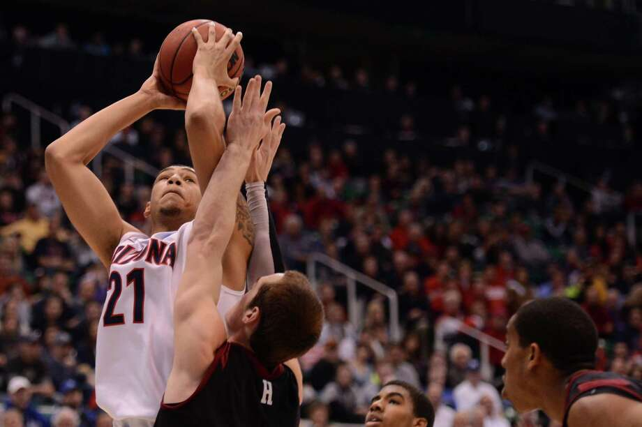 SALT LAKE CITY, UT - MARCH 23:  Brandon Ashley #21 of the Arizona Wildcats shoots over Laurent Rivard #0 of the Harvard Crimson in the first half during the third round of the 2013 NCAA Men's Basketball Tournament at EnergySolutions Arena on March 23, 2013 in Salt Lake City, Utah. Photo: Harry How, Getty Images / 2013 Getty Images
