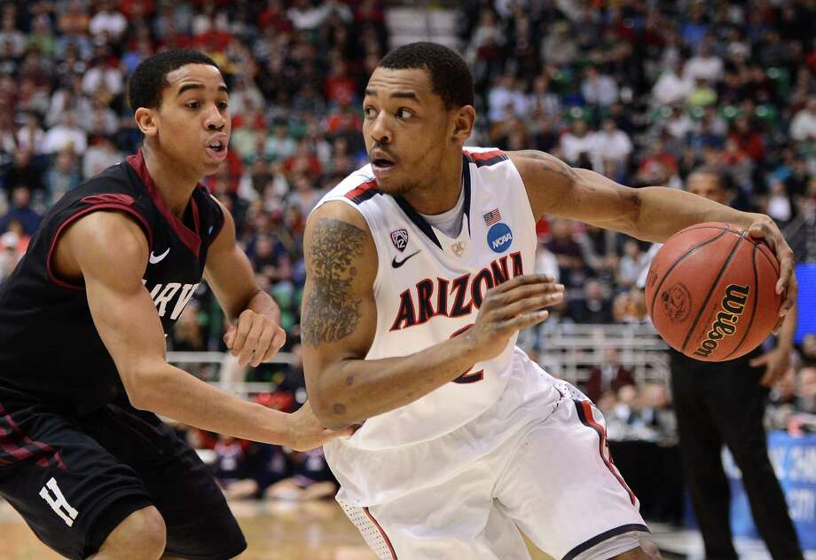 SALT LAKE CITY, UT - MARCH 23:  Mark Lyons #2 of the Arizona Wildcats drives on Siyani Chambers #1 of the Harvard Crimson in the first half during the third round of the 2013 NCAA Men's Basketball Tournament at EnergySolutions Arena on March 23, 2013 in Salt Lake City, Utah. Photo: Harry How, Getty Images / 2013 Getty Images