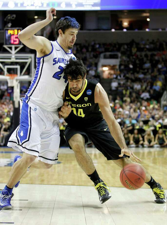 Oregon forward Arsalan Kazemi (14) drives to the basket against Saint Louis forward Cody Ellis (24) during the first half of a third-round game in the NCAA college basketball tournament Saturday, March 23, 2013, in San Jose, Calif. (AP Photo/Tony Avelar) Photo: Tony Avelar, Associated Press / FR155217 AP