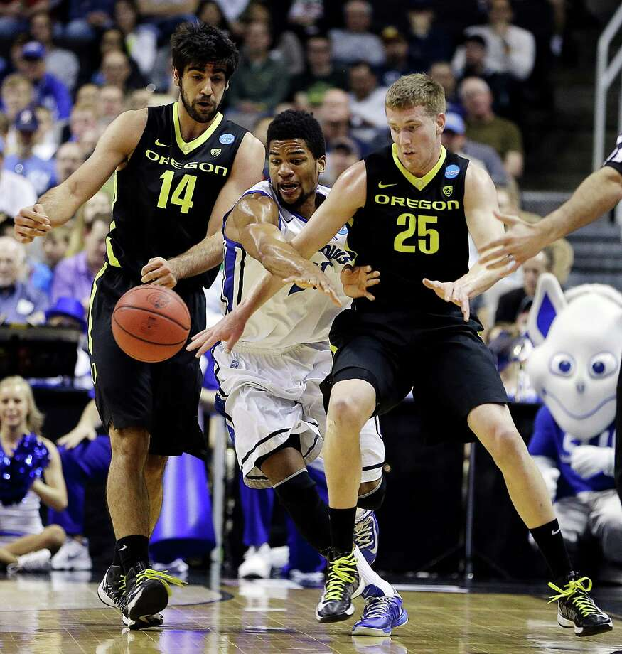 Oregon's Arsalan Kazemi (14), Saint Louis forward Dwayne Evans (21), and Oregon forward E.J. Singler (25) chase a loose ball during the first half of a third-round game in the NCAA college basketball tournament, Saturday, March 23, 2013, in San Jose, Calif. (AP Photo/Ben Margot) Photo: Ben Margot, Associated Press / AP