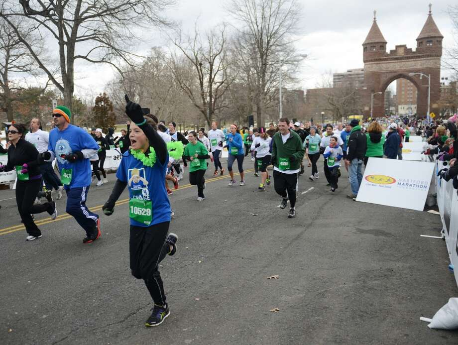 Emily Grimes, 16, of Sandy Hook, points a finger as she crosses the finish line in the Sandy Hook Run for the Families 5K in Hartford, Conn. on Saturday, March 23, 2013.  About 15,000 people participated in the event and proceeds went to the Sandy Hook School Support Fund.