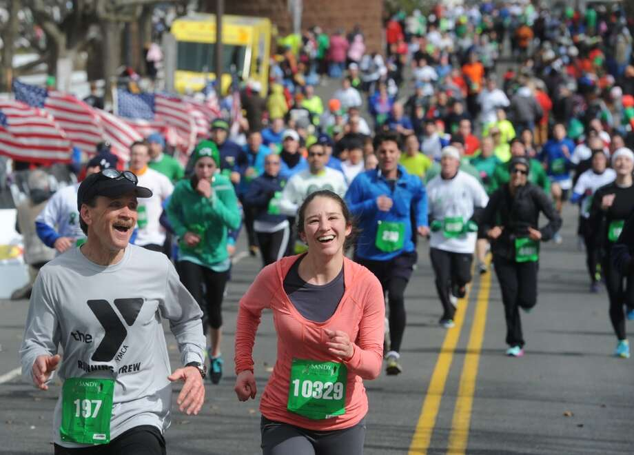 Tom Kelly and Lindsey Trachtenberg, of Hartford, cross the finish line at the Sandy Hook Run for the Families 5K in Hartford, Conn. on Saturday, March 23, 2013.  About 15,000 people participated in the event and proceeds went to the Sandy Hook School Support Fund.