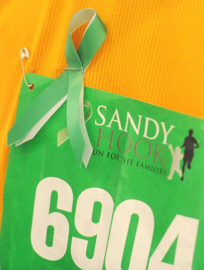 Matthew Grivner, of Woodbury, wears a commemorative ribbon by his race bib at the Sandy Hook Run for the Families 5K in Hartford, Conn. on Saturday, March 23, 2013.  About 15,000 people participated in the event and proceeds went to the Sandy Hook School Support Fund.