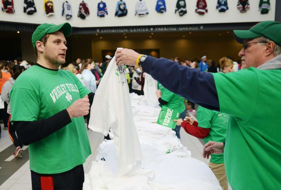 Brenton Liba, left, of Middletown, gets a shirt from Mike lowell, of Vernon, before participating in the Sandy Hook Run for the Families 5K in Hartford, Conn. on Saturday, March 23, 2013.  About 15,000 people participated in the event and proceeds went to the Sandy Hook School Support Fund.