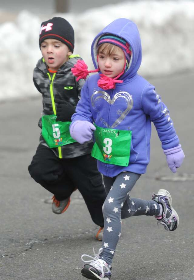 Brady Luft and MacKenna Vogel, 4-year-olds from Garrison, N.Y., participate in the kids fun run at the Sandy Hook Run for the Families 5K in Hartford, Conn. on Saturday, March 23, 2013.  About 15,000 people participated in the event and proceeds went to the Sandy Hook School Support Fund.