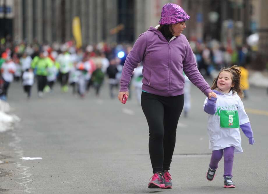 Leah Burdick, of New London, walks with her daughter, Natalie Burdick, 5, in the kids fun run at the Sandy Hook Run for the Families 5K in Hartford, Conn. on Saturday, March 23, 2013.  About 15,000 people participated in the event and proceeds went to the Sandy Hook School Support Fund.