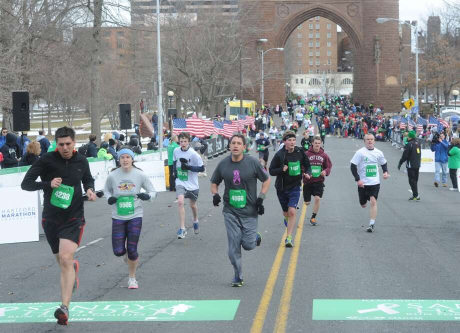 Runners cross the finish line at the Sandy Hook Run for the Families 5K in Hartford, Conn. on Saturday, March 23, 2013.  About 15,000 people participated in the event and proceeds went to the Sandy Hook School Support Fund.