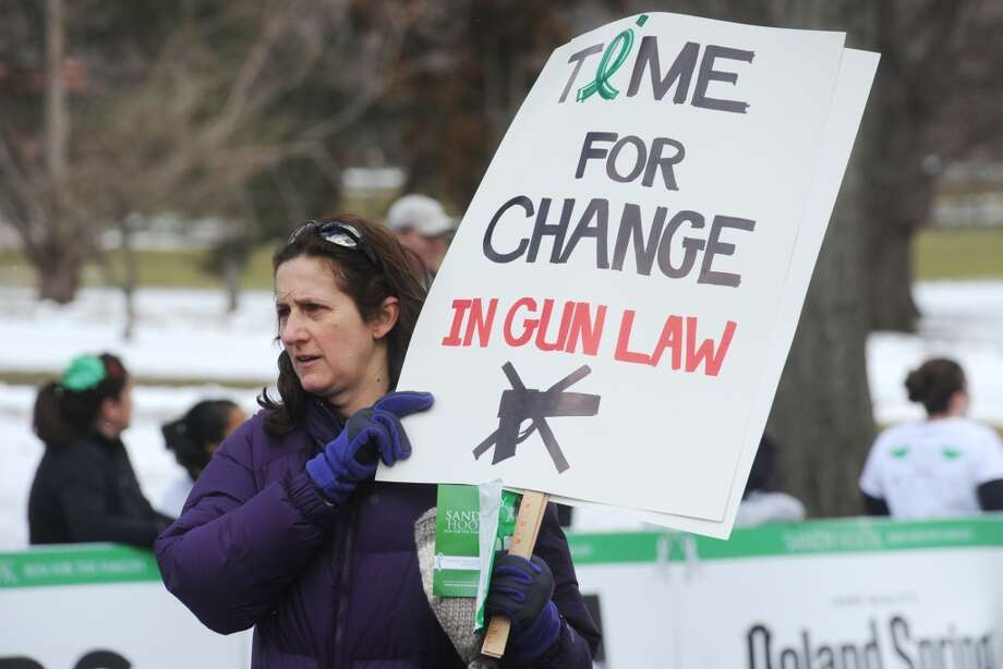 Karen Murano, of Brookfield, carries a gun reform sign while participating in the Sandy Hook Run for the Families 5K in Hartford, Conn. on Saturday, March 23, 2013.  About 15,000 people participated in the event and proceeds went to the Sandy Hook School Support Fund.