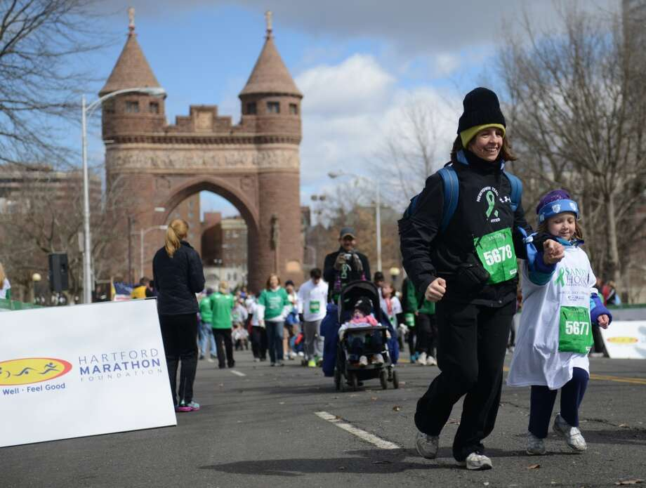 Nora Lee, of Hamden, crosses the finish line with her daughter Eleanor Lee, 5, in the Sandy Hook Run for the Families 5K in Hartford, Conn. on Saturday, March 23, 2013.  Lee's husband is a teacher at Newtown High School.  About 15,000 people participated in the event and proceeds went to the Sandy Hook School Support Fund.