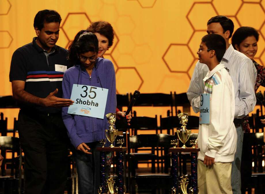 Shobha Dasari, 12,  of Leon Sablatura Middle School in Pearland, is hugged by her father Ganesh Dasari after she was named co-champion along with Syamantak Payra,right, of Westbrook Intermediate School in Clear Lake  of the 2013 HoustonPBS Spelling Bee at the Melcher Center for Public Broadcasting, Saturday, March 23, 2013, in Houston.  The top 55 spellers from 1,040 schools in 42 counties, from East Texas to Austin, competed to win the opportunity to participate in the Scripps National Spelling Bee, the nationâÄös long-standing educational promotion since 1925. The final champion of the HoustonPBS Spelling Bee wins an all-expenses-paid trip for two to Washington, D.C. to represent Houston at the Scripps National Spelling Bee during Bee Week, May 28 through May 30, 2013. Photo: Karen Warren, Houston Chronicle / © 2013 Houston Chronicle