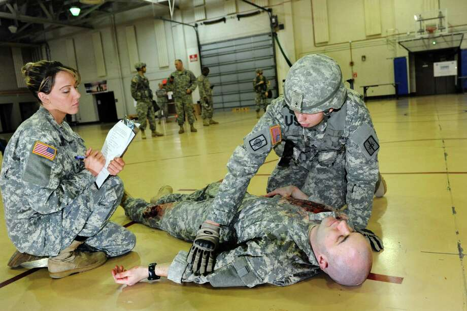 Sgt. Garrett Cummings of Troy, right, shows how to evaluate a combat casualty during the annual Best Warrior Competition on Saturday, March 23, 2013, at the Division of Military and Naval Affairs Headquarters in Latham, N.Y. Sgt. First Class Leah Marino, left, evaluates the competitors, and Specialist Thomas Rinaldi plays the casualty victim. (Cindy Schultz / Times Union) Photo: Cindy Schultz /  00021705A