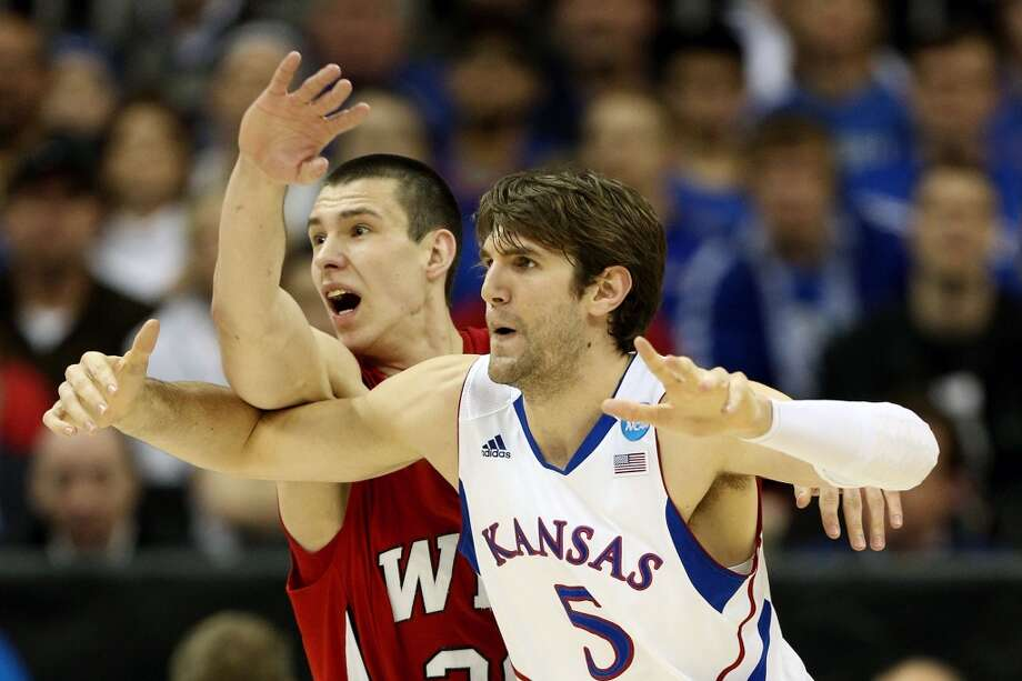 KANSAS CITY, MO - MARCH 22:  Aleksejs Rostov #20 of the Western Kentucky Hilltoppers and Jeff Withey #5 of the Kansas Jayhawks jockey for position in the second half during the second round of the 2013 NCAA Men's Basketball Tournament at the Sprint Center on March 22, 2013 in Kansas City, Missouri.  (Photo by Ed Zurga/Getty Images)