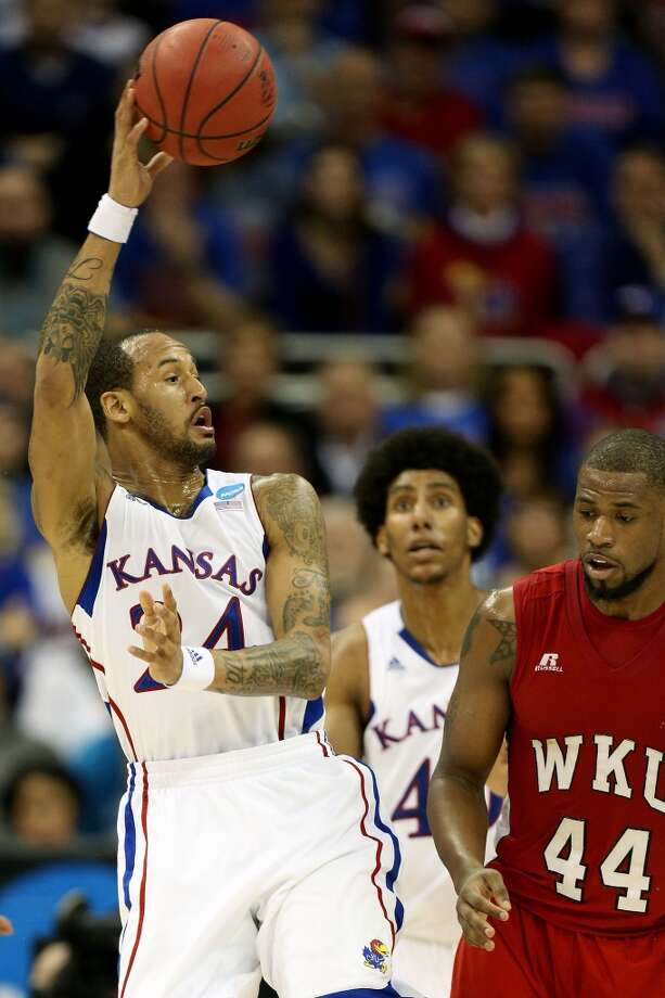 KANSAS CITY, MO - MARCH 22:  Travis Releford #24 of the Kansas Jayhawks passes against George Fant #44 of the Western Kentucky Hilltoppers in the second half during the second round of the 2013 NCAA Men's Basketball Tournament at the Sprint Center on March 22, 2013 in Kansas City, Missouri.  (Photo by Ed Zurga/Getty Images)
