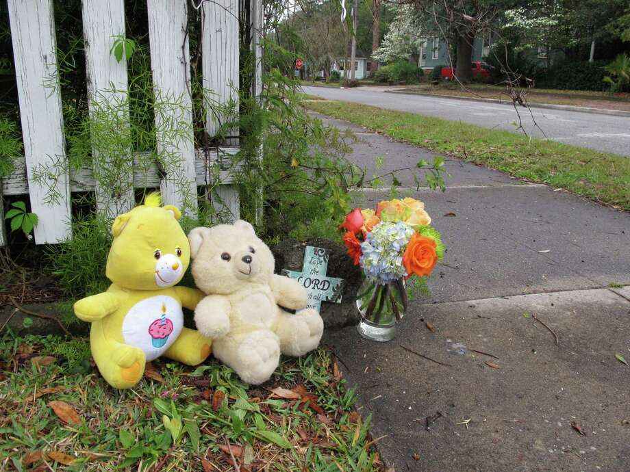Two teddy bears, a commemorative cross and a vase of flowers sit on a street corner in Brunswick, Ga. on Saturday, March 23, 2013, near where a 13-month-old baby was fatally shot in his stroller two days earlier. Sherry West says her son, Antonio Santiago, was shot in the face by a gunman after she refused to give him money. (AP Photo/The Morning News, Russ Bynum) Photo: Russ Bynum