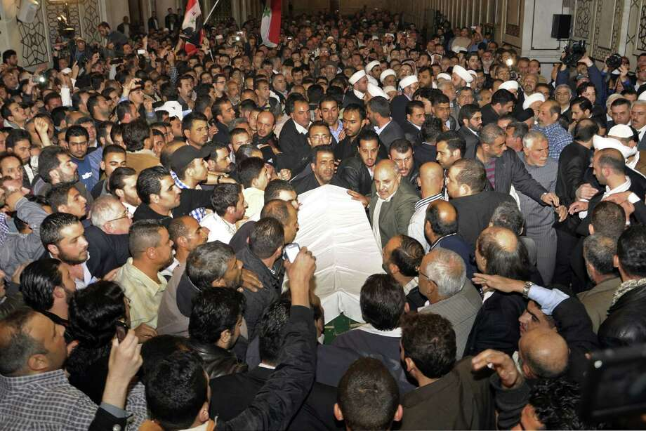 In this photo released by the Syrian official news agency SANA, mourners carry the body of Sheik Mohammad Said Ramadan al-Buti, an 84-year-old pro-government cleric during his funeral in the eighth century Omayyad Mosque, in Damascus, Syria, Saturday, March 23, 2013. Al-Buti, his grandson and scores of others were killed Thursday, March 21, 2013 when a suicide bomber detonated his explosives inside a mosque where al-Buti was giving a religious lesson. His assassination was a blow to Assad, who vowed Friday to avenge his death. (AP Photo/SANA) Photo: HOPD